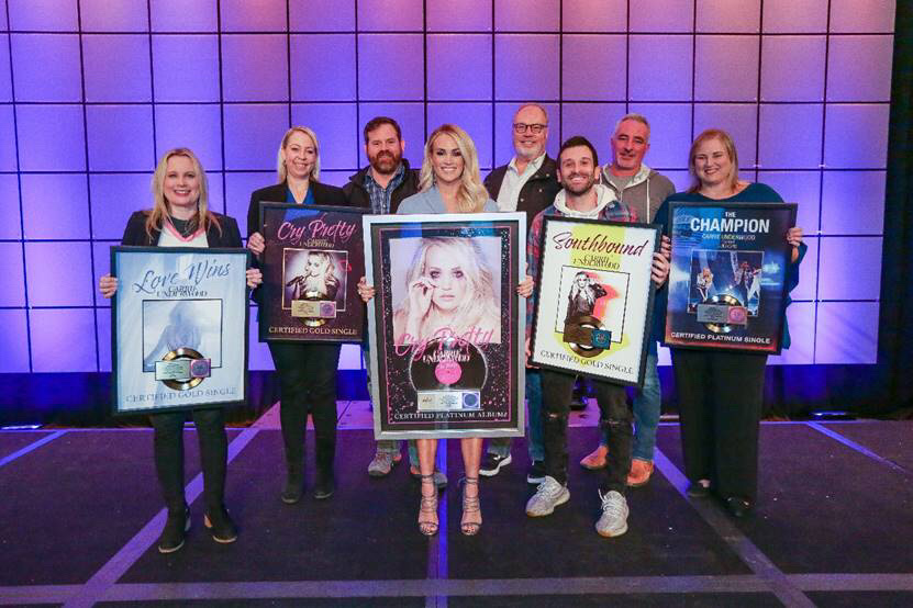 From left to right: Cindy Mabe (President, UMGN), Ann Edelblute (Owner, The HQ), Royce Risser (EVP of Promotions, UMGN), Carrie Underwood, Mike Dungan (Chairman & CEO, UMGN), David Garcia (Underwood's Co-Producer), Brian Wright (EVP of A&R, UMGN), Jackie Jones (Vice President, Artist & Industry Relations, RIAA)   Photo Credit: Country Radio Seminar 2020/Kayla Schoen